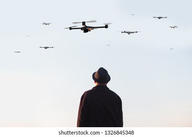 man looking at the sky filled with drones