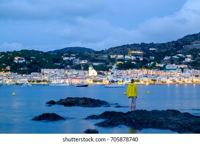 man looking at the small village of Port de la Selva at sunset