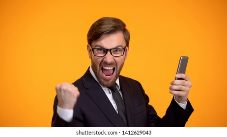 Man looking at smartphone and doing yes sign, favorable credit term, betting