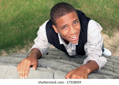 Man looking up smiling as he climbs wall