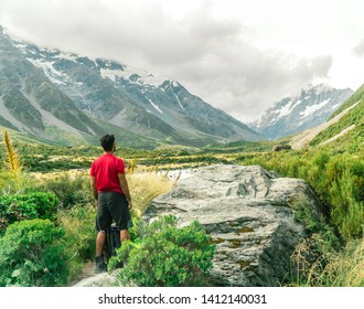 Man looking at the Snow capped Mount Cook Mountain background. On the Hooker trail tramping trek. Dramatic. Grey cloudy moody. Green outdoors nature concept. Shot in Pukaki, New Zealand.