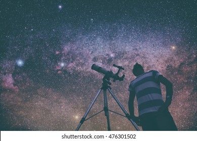 Man looking at the stars with telescope beside him. My astronomy work.