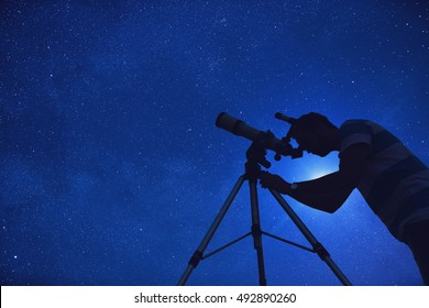 Man looking at the stars through a telescope.