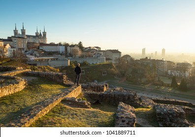 Man looking at the sunrise over Lyon from Theatre Gallo Romain, the ancient Roman theatre of Fourvier in Lyon, France.