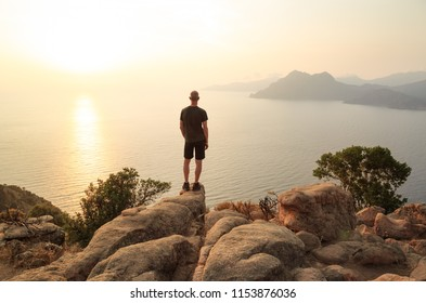 Man looking at the sunset over the sea from the cliffs. Golf of Porto, Corsica, France.
