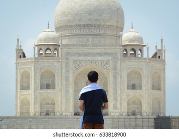A man looking at the Taj Mahal in Agra, India. The Taj Mahal is an ivory-white marble mausoleum on the south bank of the Yamuna river in the Indian city of Agra.