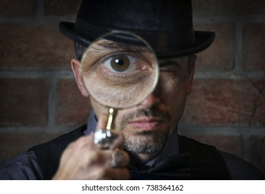 Man looking though a magnifying glass