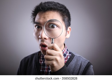 Man looking through a big magnifying glass.