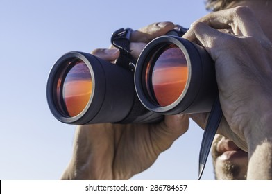 A man looking through the binoculars