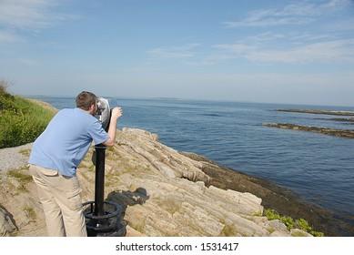 Man looking through binoculars Location: Land's End in Maine