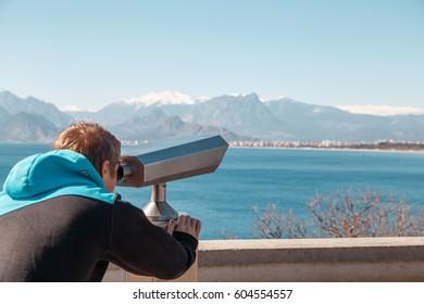 A man looking through coin binoculars on fantastic mountain lookout in Antalya, Turkey. Tourist Telescope