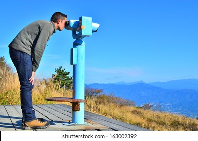 A man looking through coin operated high powered binoculars on a scenic mountain lookout.