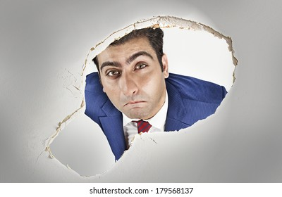Man looking through a hole in the ceiling