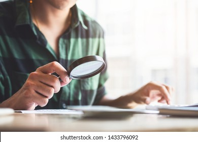 Man looking through a magnifying glass to documents. Business assessment and audit. Magnifying glass on a financial report. Close-up Of person Checking Bills With Magnifying Glass.Concept of search