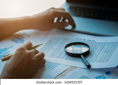 man looking through a magnifying glass to documents. Business assessment and audit. Magnifying glass on a financial report. Close-up Of Businessperson Checking Bills With Magnifying Glass.