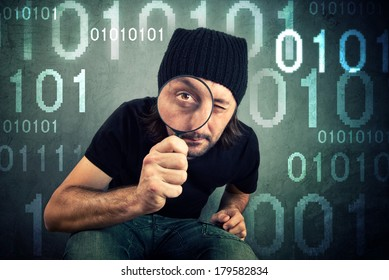 Man looking through magnifying glass and inspecting encrypted binary code.