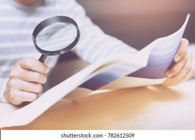 man looking through a magnifying glass to documents notebook.