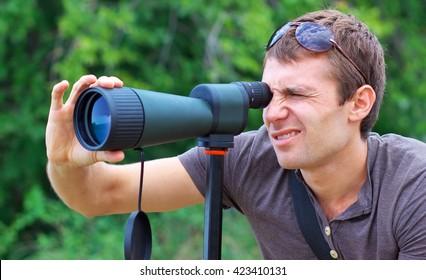 Man looking through a telescope (spotting scope).
