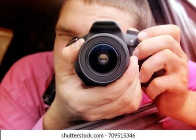 Man looking through the viewfinder of the left-handed camera lens is pointing at the viewer takes the picture from the window of the car. Out of focus