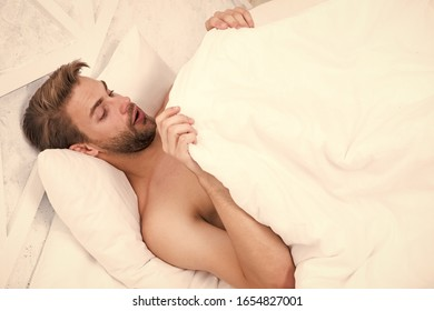 Man looking under blanket. Morning wood formally known nocturnal penile tumescence common occurrence. Male reproductive system. Why men get morning erections. Normal erections occur. Guy relax in bed.