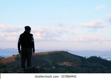 A man looking at the view in the morning at the mountain