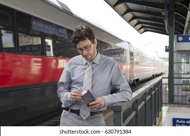 Man looking at wallet at train station.