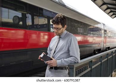 Man looking at wallet at train station