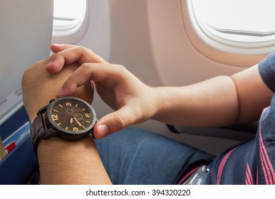 The man looking to the watch on the airplane for urgent period concept