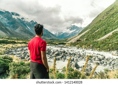 Man looking at water stream on the Hooker trail tramping trek. Dramatic. Snow capped Mount Cook Mountain background. Grey cloudy moody. Green outdoors nature concept. Shot in Pukaki, New Zealand.