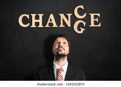 "man looking up to the words  ""change"" and ""chance"" on slate background"
