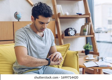 Man looking at wristwatch on sofa in living room