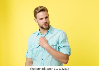 Man looks attractive casual linen blue shirt. Guy bristle undress casual shirt. Fashion concept. Man calm serious face confidently unbuttoning shirts collar, yellow background. Take off my clothes.