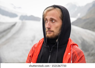 A man looks away on the background of a glacier. Red raincoat, black warm clothes. Portrait of a tourist with a surprised face. Blond with blue eyes, a beard. Mountain Altai. Cold snow.