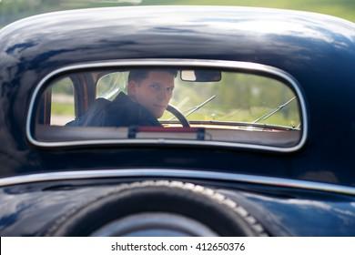 Man looks back thru the cars window