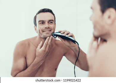 Man Looks at Bathroom Mirror and Shaving Beard. Portrait of Smiling Handsome Brown Haired Young Person with Bare Chest Using Electric Shaver and Looking at Mirror Reflection. Morning Concept