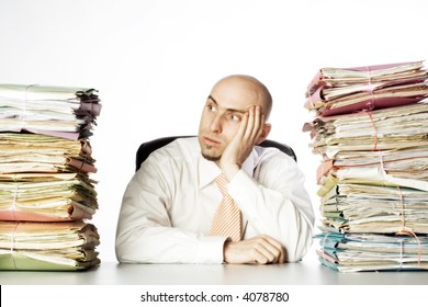 Man looks to be defeated by the piles of paperwork that flank him on either side.  Model is adult male and bald.  He has a short beard and is holding his head in one of his hands.