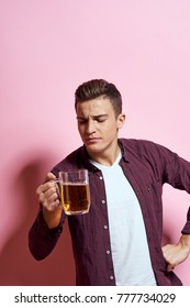 man looks at beer on a pink background, alcoholism