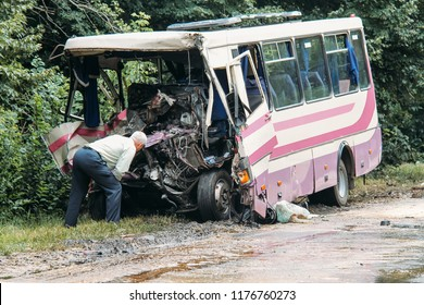 Man looks at the broken bus after the accident