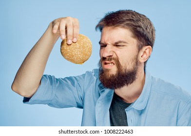 man looks at the burger, disgusted