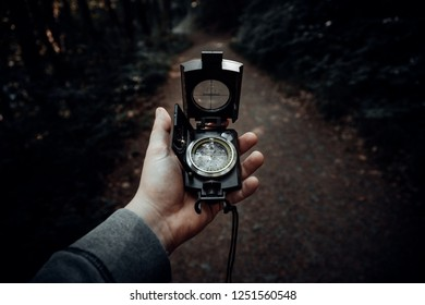 Man looks at a compass in a forest
