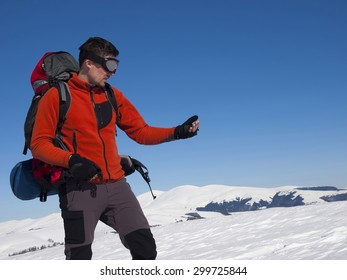 The man looks at the compass on the background of snow-capped mountains and blue sky.