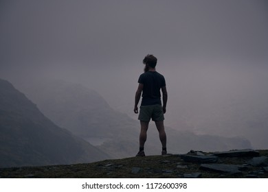 A man looks down from high in the Lake District UK onto a misty scene
