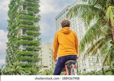 man looks at Eco architecture. Green cafe with hydroponic plants on the facade. Ecology and green living in city, urban environment concept. Modern building covered green plant