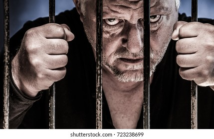 a man looks evil through the bars of a prison