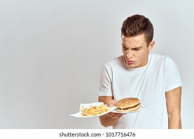 man looks at fast food on a light background