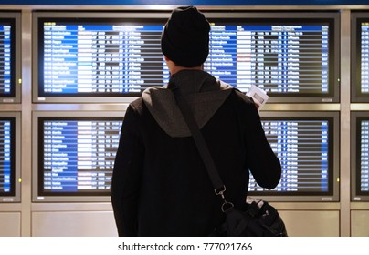 Man looks at flight schedule at Airport departure time table, Concept Travel back home on holiday christmas new year season. He ready to check in as boarding pass in hand with passport
