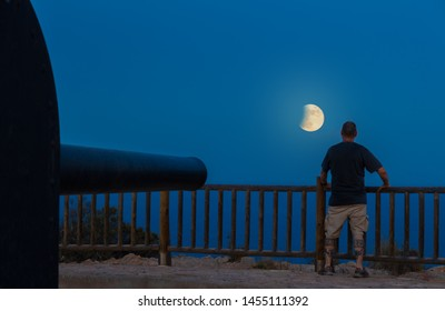 A man looks at the full moon with partial lunar eclipse. A gun is aimed at the horizon. The place is a Spanish defensive facility near the city of Cartagena.