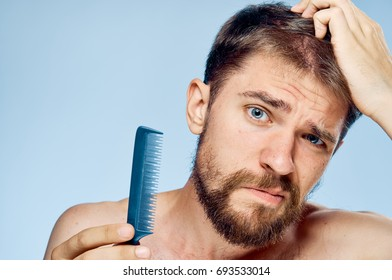A man looks into the camera adjusts his hair and holds a comb in his hand on a blue background