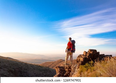 The man looks into the distance with mountains