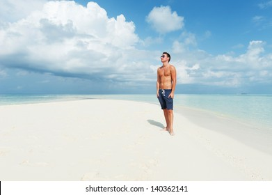 Man looks into the distance on the background of beautiful beach with white sand and cloudy sky